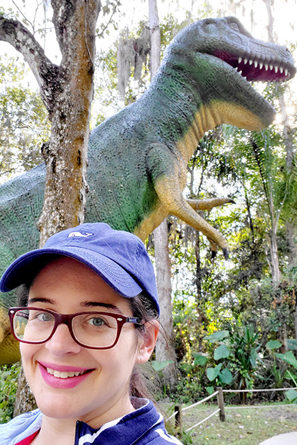 Smiling women with large dinosaur in the background