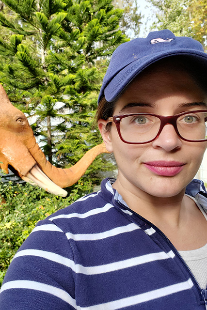 selfie photo of women in blue hat with fake mamouth in background