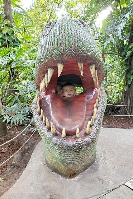 Kids pose in mouth of dinosaur