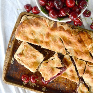 Overhead view of Cherry Slab Pie on baking sheet with overflowing bowl of cherries at top of screen
