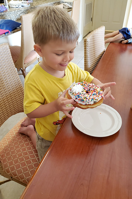 Little boy eating large donut with white glaze and sprinkles on it