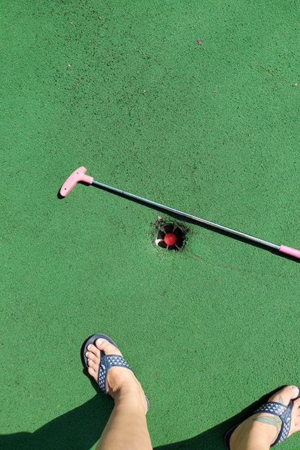 golf ball in miniature golf course hole with putter next to the hole