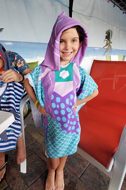 Little girl wearing mermaid towel at water park