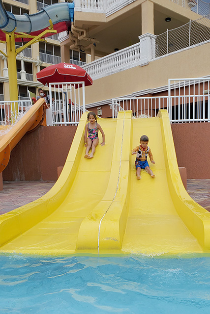 Little girl and little girl going down yellow slide at Ship Wreck Water Park