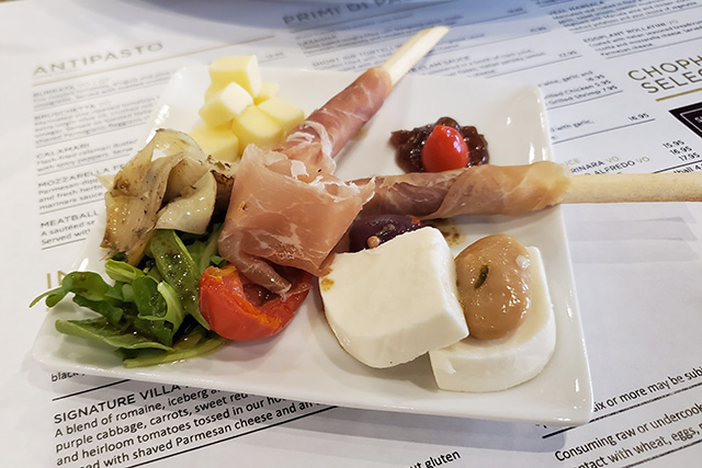 small plate of antipasto placed on a menu in an Italian Restaurant