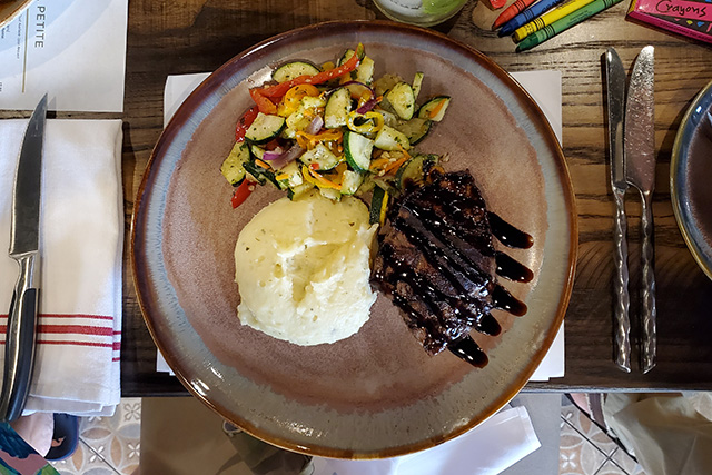 Steak with drizzle of glaze on it with mashed potatoes and sauteed vegetables