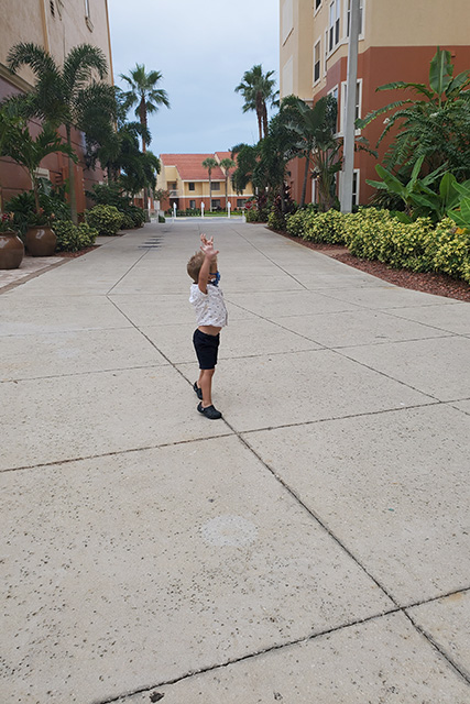little boy wearing a mask on a walk way at Westgate Town Center Resort