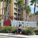 family standing with their dogs in front of I Love Westgate sign at resort in Orlando FL