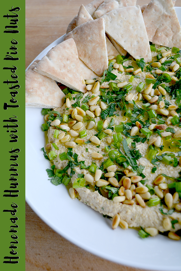Large white bowl of homemade hummus topped with toasted pine nuts, scallions, and parsley with pieces pita