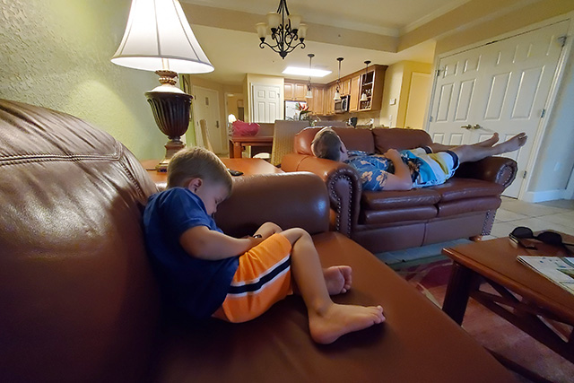 Little boy and dad taking naps on sofas in Deluxe Room at Westgate Resort