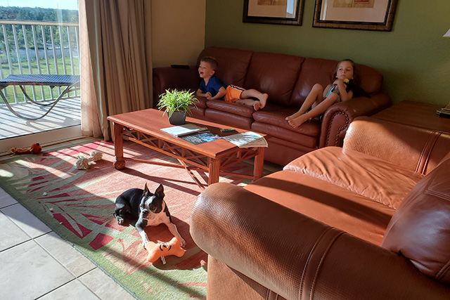 Kids watching TV on a brown leather sofa with dog in front of them at Deluxe Room at Westgate Tower Resort