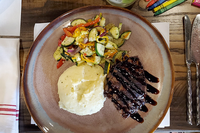Sauteeed vegetables, mashed potatoes, and steak with a glaze drizzled on top on a rustic plate at Italian Restaurant