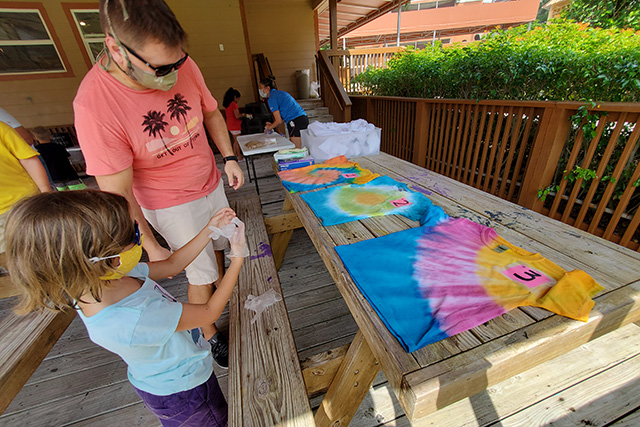 Little girl getting on gloves to do tie dye project