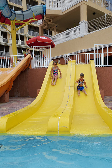 Little girl and little boy going down a small yellow water slide at a water park