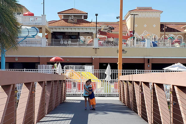 Little boy and llittle girl standing on wooden bridge in front of water park at Westgate Resort