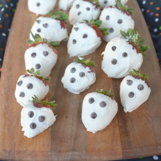 chocolate covered strawberry ghosts on a wooden serving board on halloween napkin