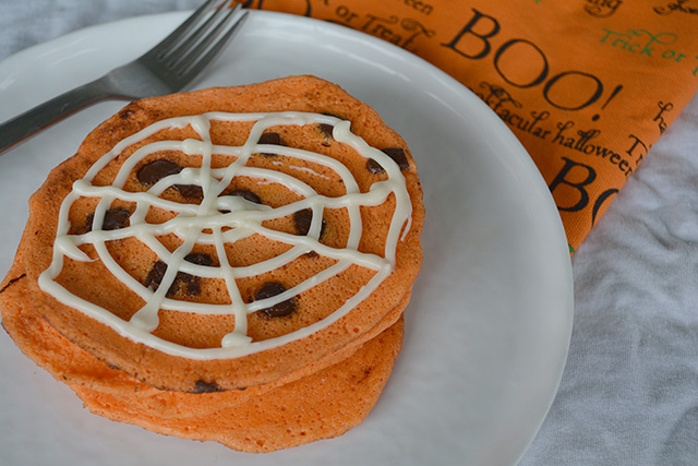 Stack of orange chocolate chip pancakes with a spider web design on top with cream cheese frosting