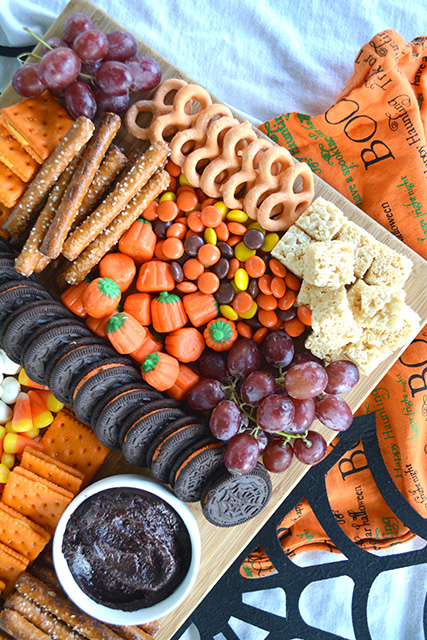Halloween Themed Dessert Charcuterie Style Board with candy corn, grapes, dessert hummus, pretzels, Reese's Pieces, mini candy pumpkins, and more