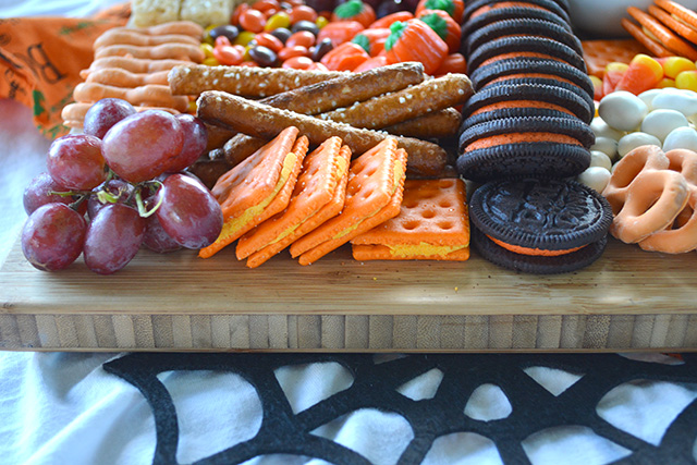 side view of Halloween Themed Dessert Charcuterie Style Board with Halloween Sandwich Cookies, grapes, and cheese crackers