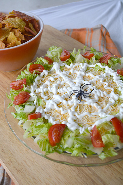 Halloween theme taco dip with a sider web on top made of sour cream