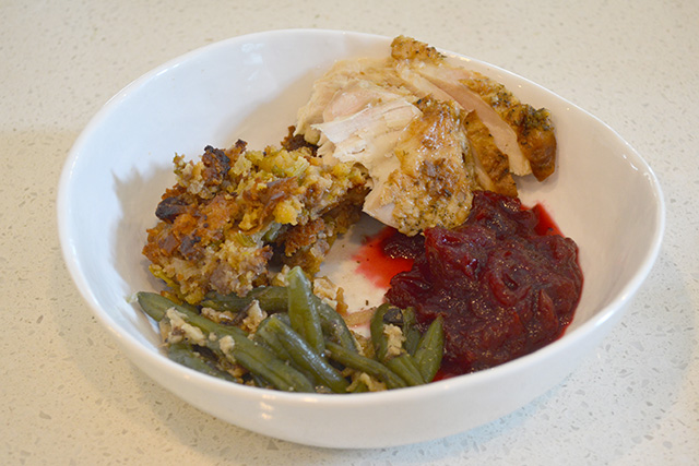 large shallow bowl of Thanksgiving Leftovers of turkey, stuffing, cranberry sauce, and green beans
