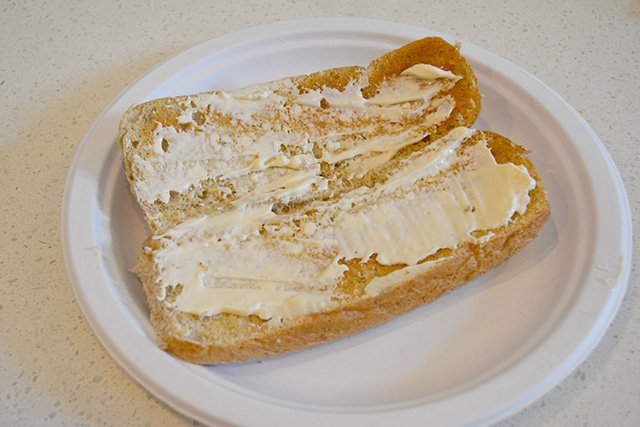 Generous amount of mayo on a toasted sandwich roll