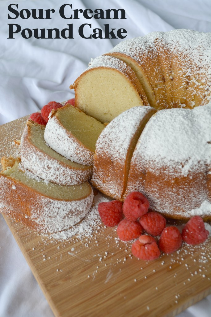 powered sugar dusted Sour Cream pound Cake in a bundt shape on wooden cutting board