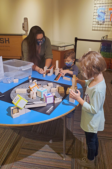mom and 2 kids playing with blocks at museum exhibit