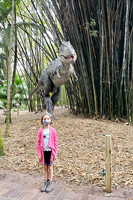 little girl standing in front of a dinosaur statue at Leu gardens during Dinosaur Invasion