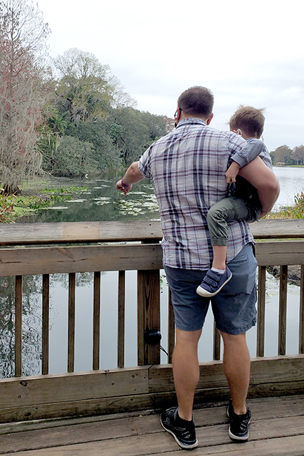 man holding litle boy on his hip standing on a dock pointing to the water