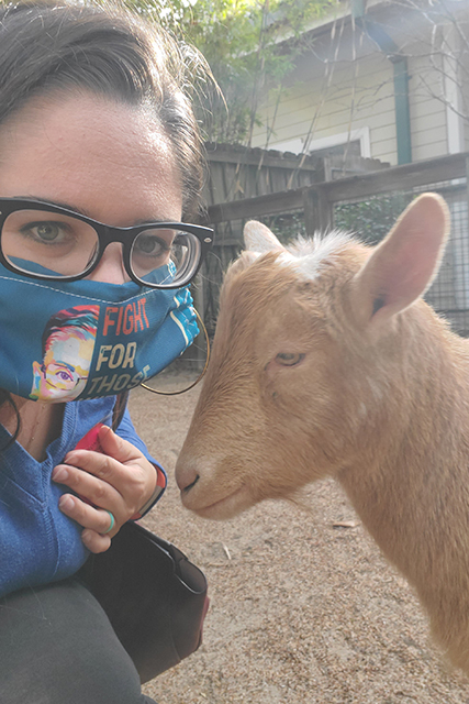 woman wearing a mask taking a selfie with a Nigerian Dwarf Goat