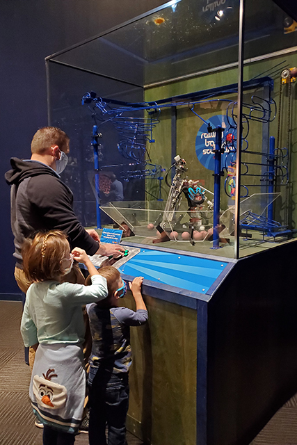 family playing with a mechanical game that picks up balls to go on spiral rail system