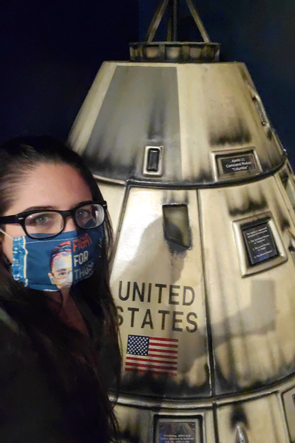 woman wearing a mask taking selfie in front replica space ship capsule from Apollo missions at Jacksonville MOSH