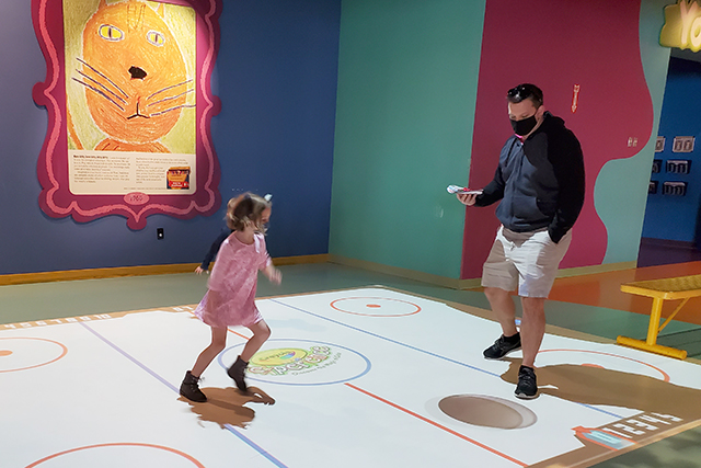 kids playing digital air hockey that has been displayed on floor