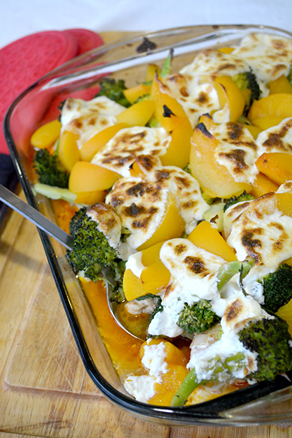 Chicken Broccoli Peach Bake in a pan with a serving spoon picking up some of the casserole