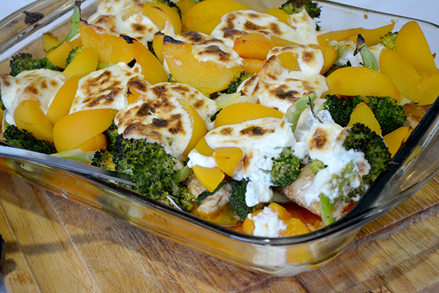 Chicken Broccoli Peach Bake in a glass pan on a wooden cutting board