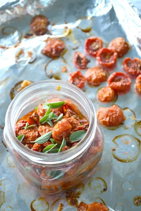 wide mouth jar filled with oil and slow roasted tomatoes on a foil lined sheet pan