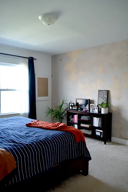 Bedroom with bookcase in front of ginkgo print wallpaper with sunlight shining in from windows.