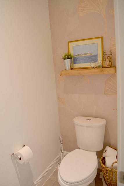 Toilet closet with wall paper accent wall behind toilet with shelf with picture and accents on it.