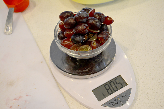 Halves and quartered red grapes in a bowl on a scale.