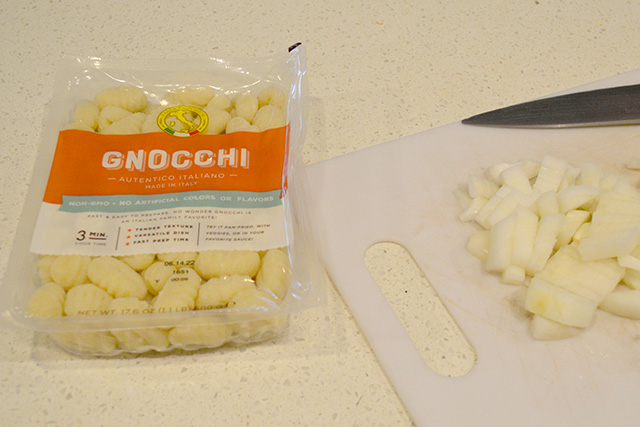 Package of potato gnocchi next to diced onion on cutting board.
