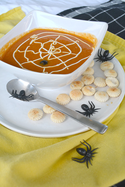 Bowl of Roasted Tomato Pumpkin Soup on a plate with oyster crackers.