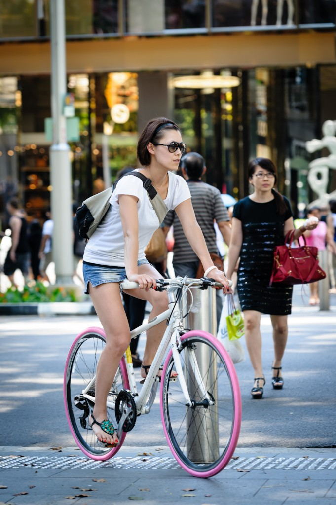 Street photography - Girl riding a bicycle with pink tyres in Orchard Singapore