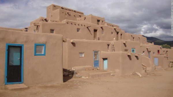 [UNVERIFIED CONTENT] Taos Pueblo (or Pueblo de Taos) is an ancient pueblo belonging to a Taos (Northern Tiwa) speaking Native American tribe of Pueblo people. It is approximately 1000 years old and lies about 1 mile north of the city of Taos. A reservation of 95,000 acres is attached to the pueblo, and about 1,900 people live in this area. Taos Pueblo's most prominent architectural feature is a multi-storied residential complex of reddish-brown adobe divided into two parts by the Rio Pueblo. It is believed to have been built between 1000 and 1450 A.D. It was designated a National Historic Landmark on October 9, 1960, and in 1992 became a World Heritage Site. As of 2006, about 150 people live in it full-time.