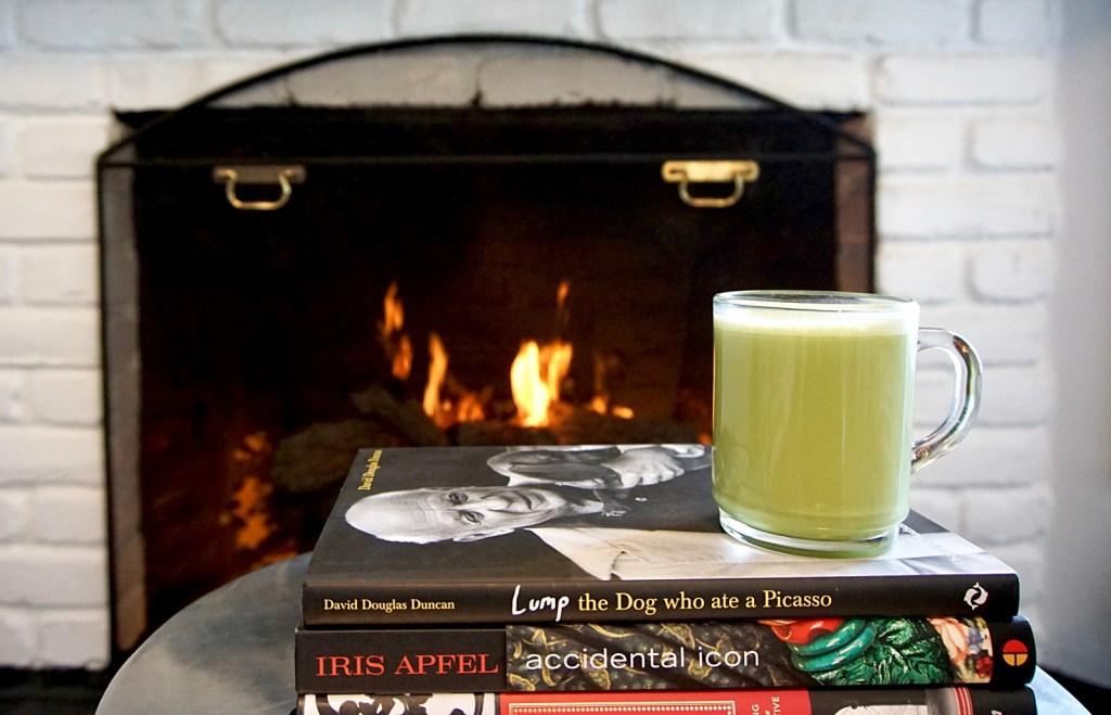 A bulletproof matcha latte in a glass cup by the fireplace.