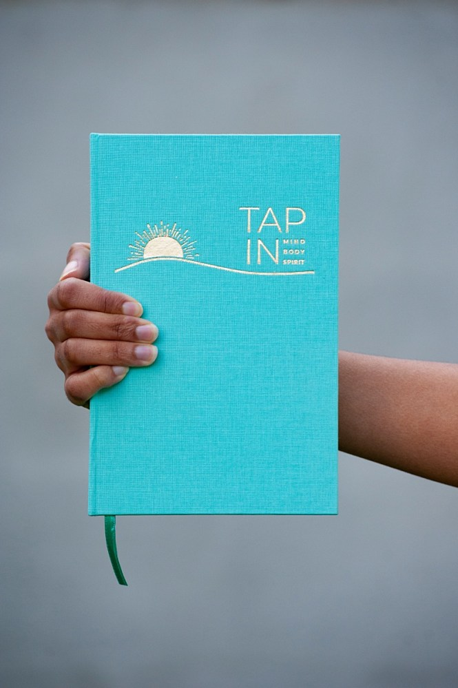 A hand holding TAP IN wellness journal
