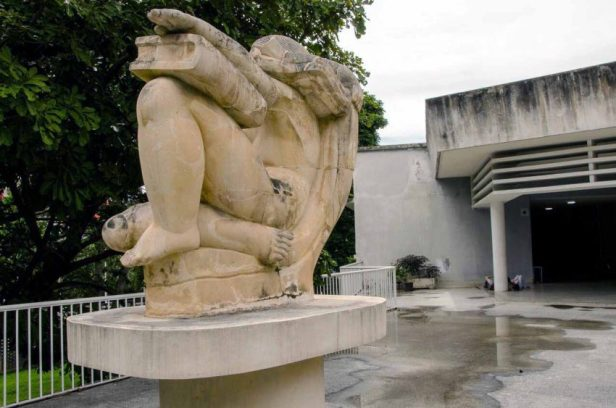 Al fondo se observa el techo con una pátina negra por acumulación de mugre y hollín. En primer plano la obra La Educación, de Francisco Narváez. Ciudad Universitaria de Caracas, Patrimonio mundial de Venezuela 2000.