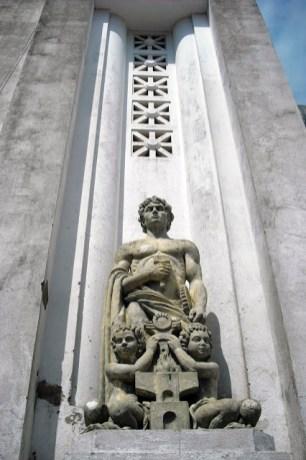 Edificio Nacional de San Cristóbal, estado Táchira. Escultura alegórica de la Industria y ventanales romanos calados en forma de aspa en el moldurado cajeado del muro. Foto Samir Sánchez, 2016.