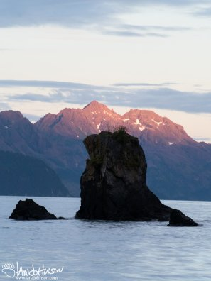 A rock island stands in front of the alpen glow in Alaska.