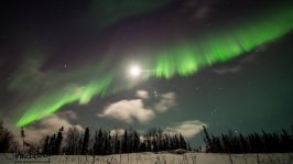 A brilliant green curtain of aurora stretches across the moon.